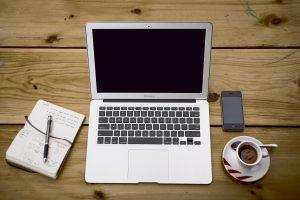 computer, kaffe og notesblok