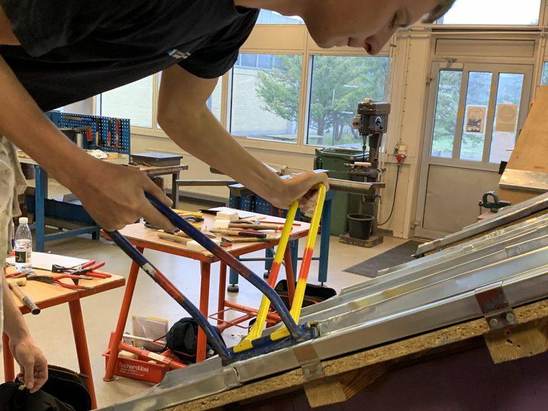 Lærling arbejder på et zinktag på et modelhus