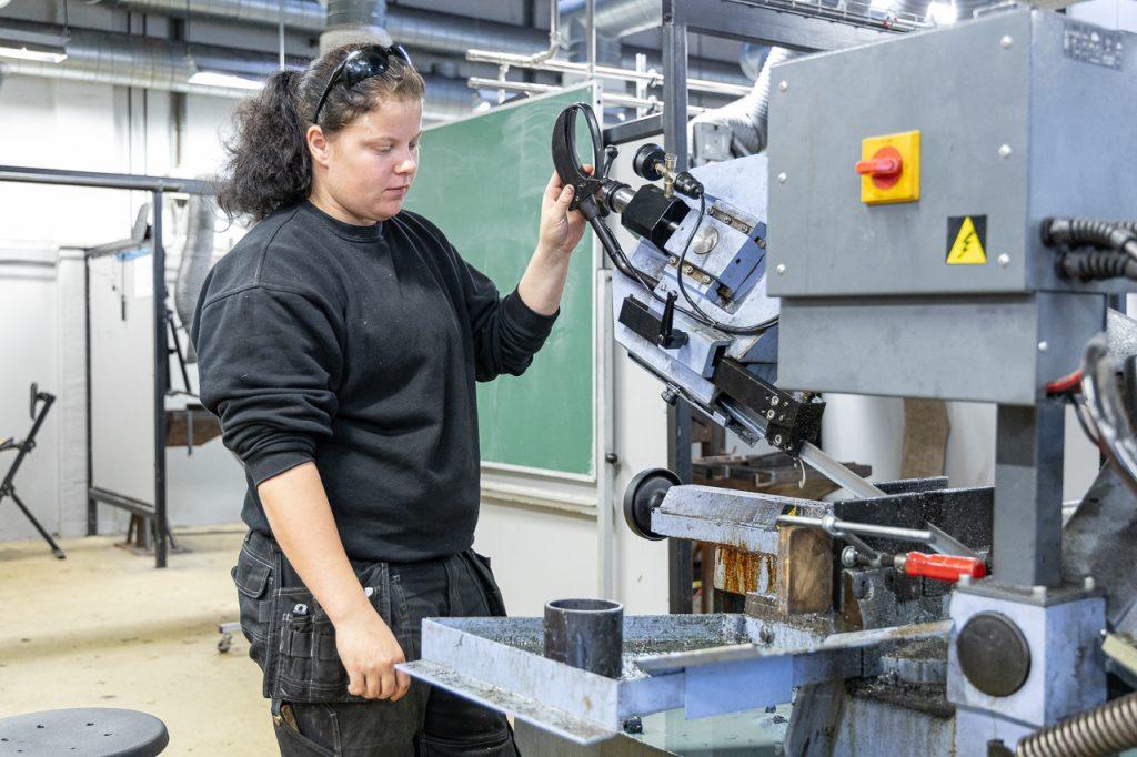 Installationsteknikerlærlingen Frederikke ved en maskine